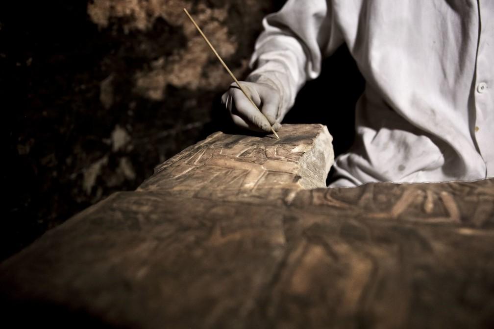 Arqueologista recupera uma estátua dentro da tumba encontrada perto de Sacará — Foto: Nariman El-Mofty/AP
