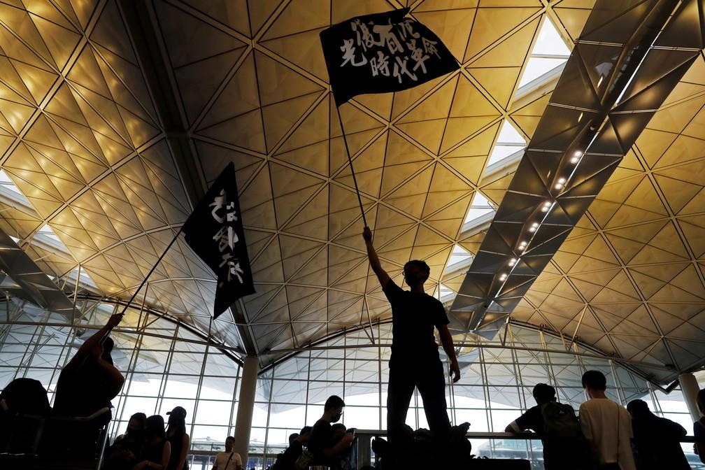 """Manifestante segura uma bandeira com caracteres chineses que dizem """"LIbertem Hong Kong, a revolução de nossos tempos"""" em uma manifestação no aeroporto da cidade nesta segunda-feira (12).  — Foto: Tyrone Siu/Reuters"""