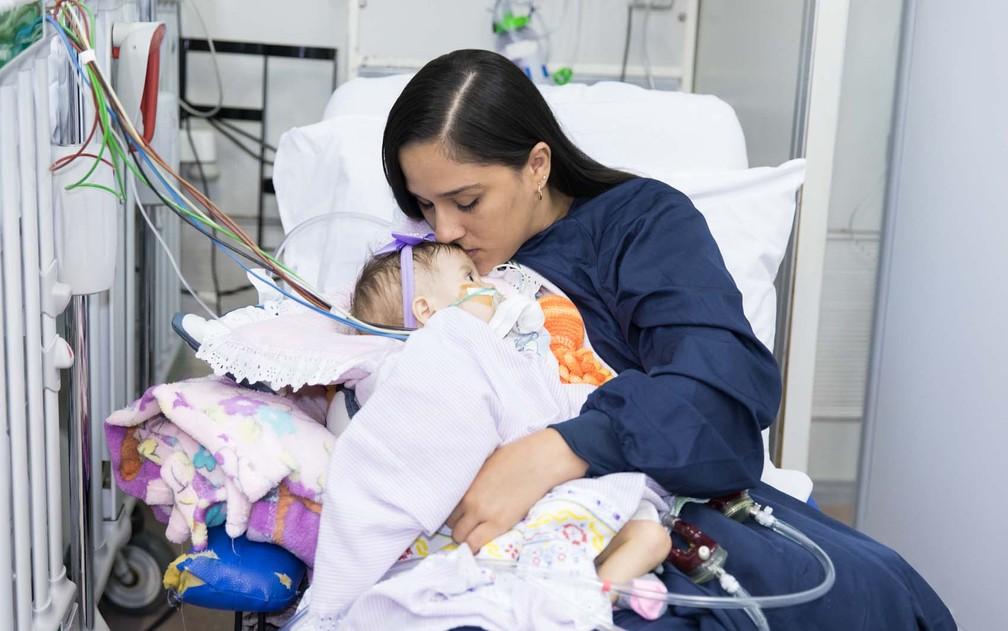Larissa beija a testa da filha Lorena na UTI do Incor (Foto: Celso Tavares/G1)