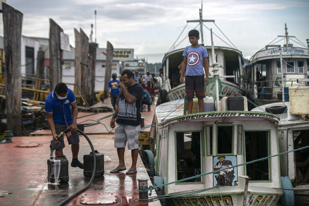 Membros de comunidades ribeirinhas abastecem embarcação antes de ir embora em Breves, no Pará, a sudoeste da Ilha de Marajó. — Foto: Tarso Sarraf/AFP