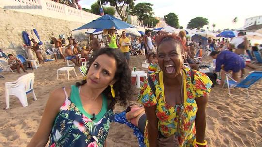 Maria curte a praia da Barra ao lado de figuras pitorescas