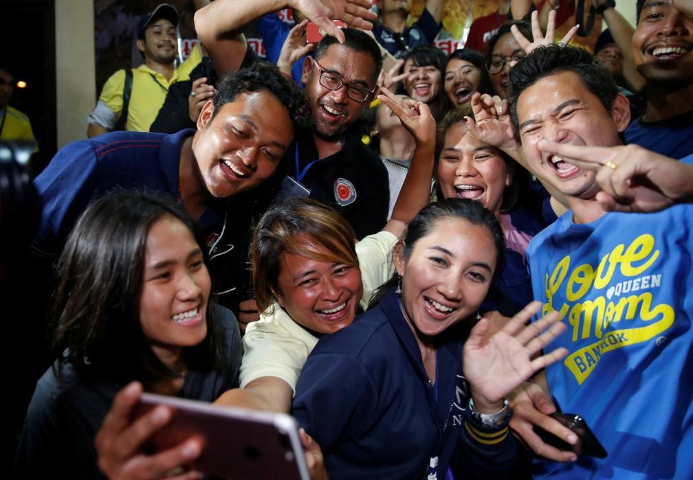 10 de julho - Jornalistas comemoram resgate dos meninos e do treinador após entrevista coletiva perto do complexo de cavernas de Tham Luang, na Tailândia  (Foto: Soe Zeya Tun/Reuters)