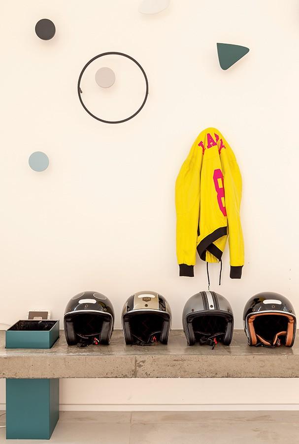Dupla funcionalidade: no hall de entrada, o móvel de concreto serve como prateleira e banco, e os cabideiros inspirados nas obras do artista Calder (criação da WF Arquitetos com o Estúdio Rika) também enfeitam (Foto: Ricardo Bassetti)