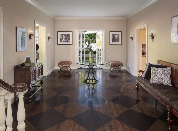 O hall de entrada dá direto na escadaria que leva ao segundo andar e conecta a entrada aos fundos da casa (Foto: Berkshire Hathaway HomeServices/ Reprodução)