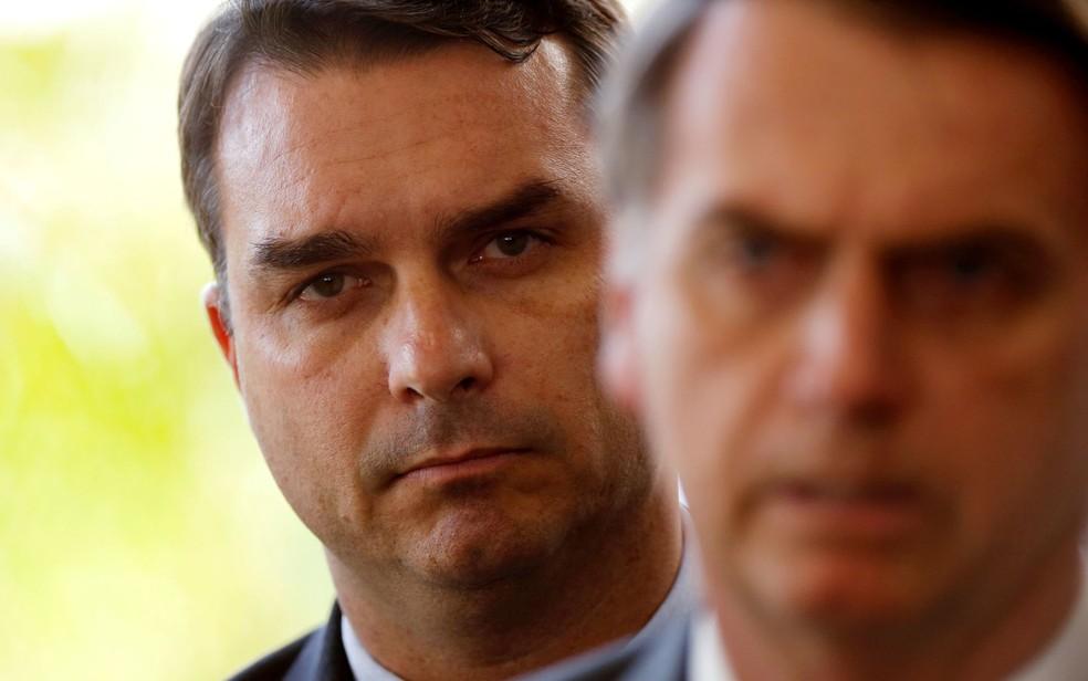 O presidente Jair Bolsonaro e, ao fundo, seu filho Flávio Bolsonaro, em imagem de novembro de 2018 — Foto: Adriano Machado/Reuters