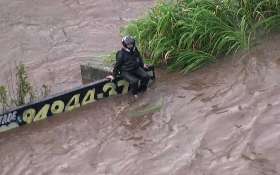 Motociclista se protege de alagamento sobre muro em Santo André — Foto: Reprodução/TV Globo