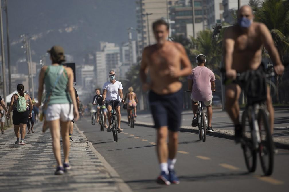Cariocas se exercitam no calçadão da praia de Ipanema - muitos não usaram máscaras, o que é proibido — Foto: Silvia Izquierdo/AP
