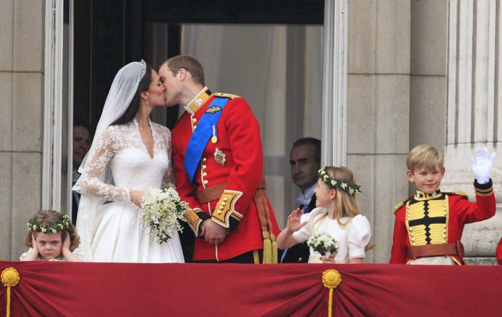 Dama de honra olha o casal se beijando durante saudação aos súditos (Foto: AP )