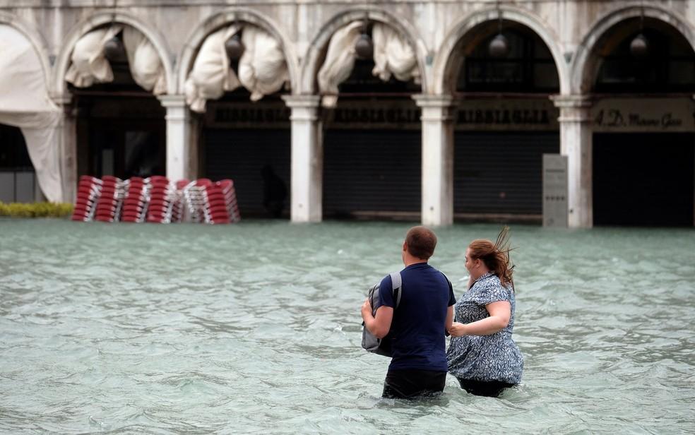 Casal caminha pela Praça São Marcos alagada, em Veneza, na segunda-feira (29) — Foto: Reuters/Manuel Silvestri
