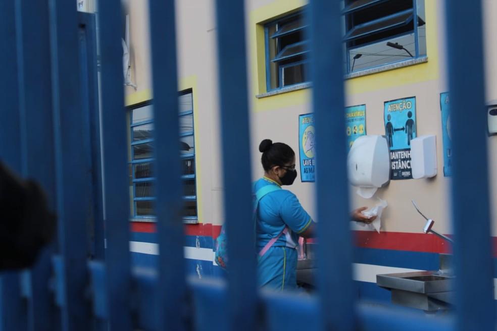 Aluna higieniza mãos antes de entrar na sala de aula — Foto: Eliana Nascimento/G1 AM