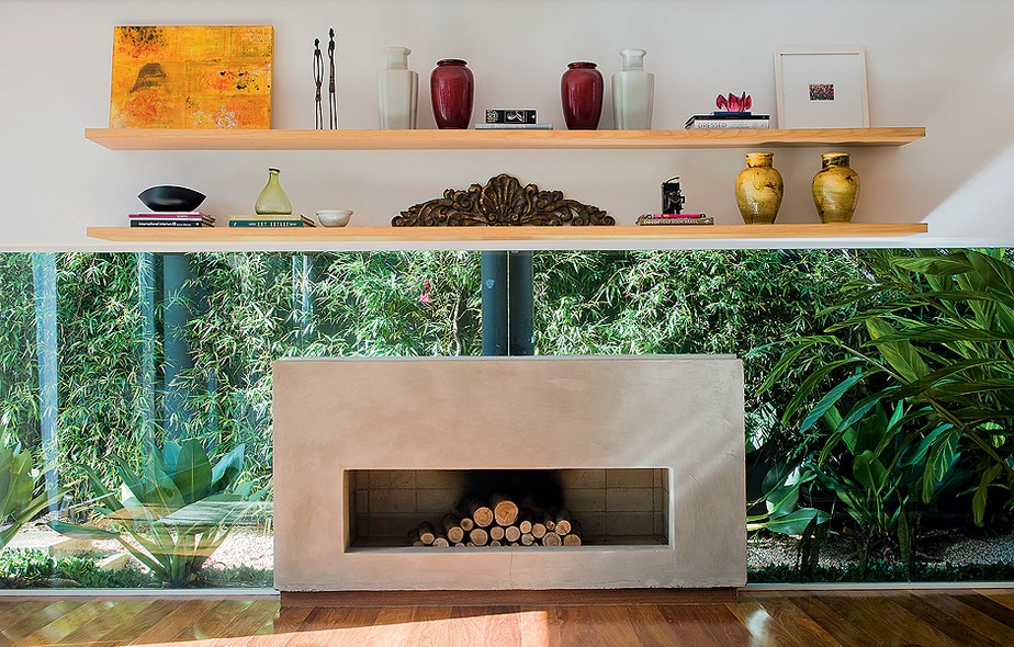 """A sala tem panos de vidro por todos os lados. A arquiteta Vanessa Féres não queria interferir na vista para o jardim, mas precisava de um local para os adornos. Ela projetou prateleiras acima da lareira. """"Desta forma, dei destaque ao local"""", afirma"""