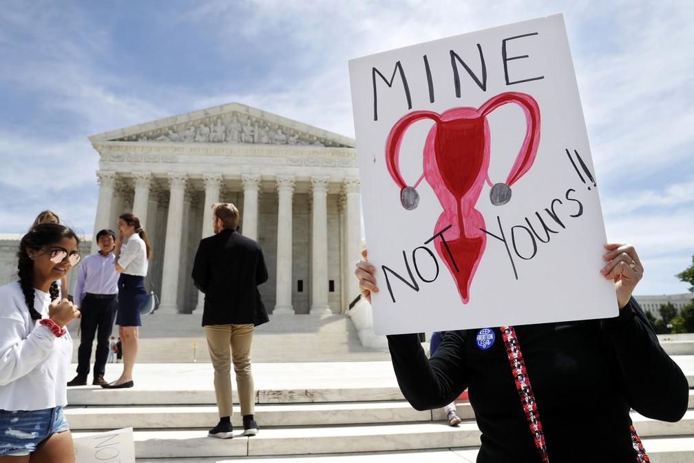 """Na foto, Laurie Ploch segura um desenho de um útero com os dizeres """"meu, não seu"""" em frente à Suprema Corte em Washington, capital dos Estados Unidos. — Foto: Jacquelyn Martin/AP"""