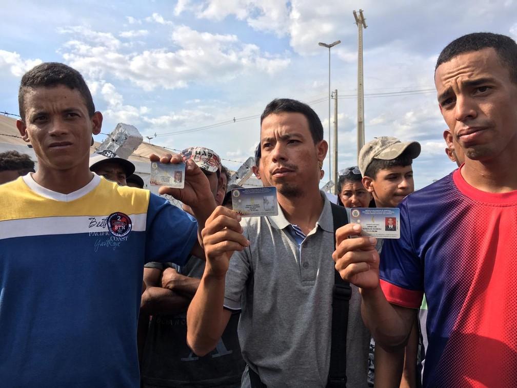 Militares venezuelanos que desertaram para o Brasil mostram suas identidades em Pacaraima, em Roraima — Foto: Emily Costa/G1