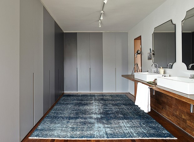 No espaço criado pela arquiteta Daniela Ruiz, os armários em tons de cinza dividem o ambiente com as cubas, os espelhos e a bancada deslocadas da área interna do banheiro para o closet (Foto: Victor Affaro/Editora Globo)