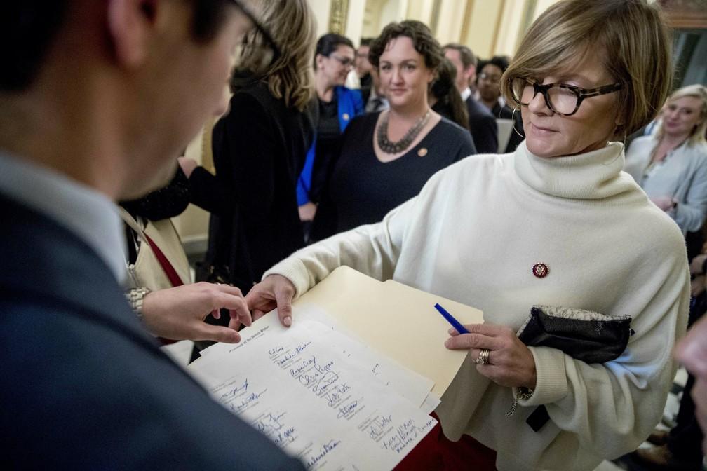 Deputada democrata Susie Lee pede assinaturas para carta que pede o fim da paralisação do governo para ser entregue ao senador republicano Mitch McConnell — Foto: Andrew Harnik/AP Photo