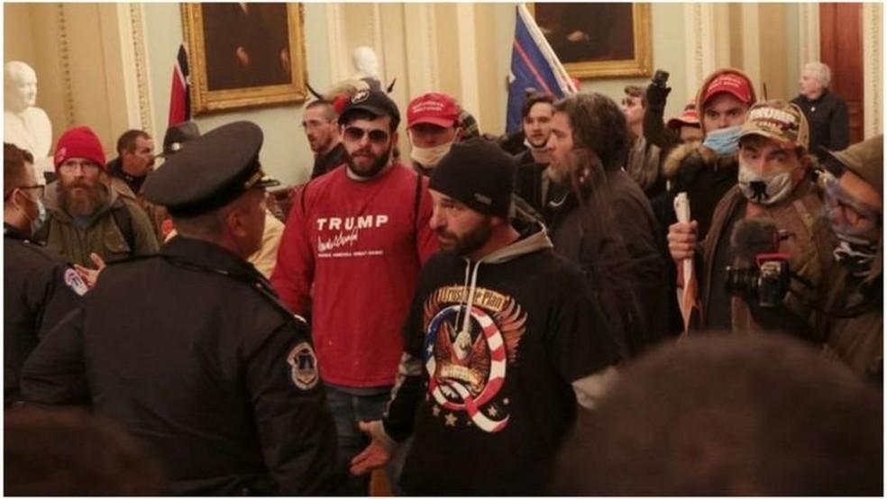 Um manifestante vestindo uma camisa com o slogan do QAnon 'Confie no plano' fala com a polícia dentro do prédio do Capitólio dos EUA na quarta-feira — Foto: Getty Images/BBC