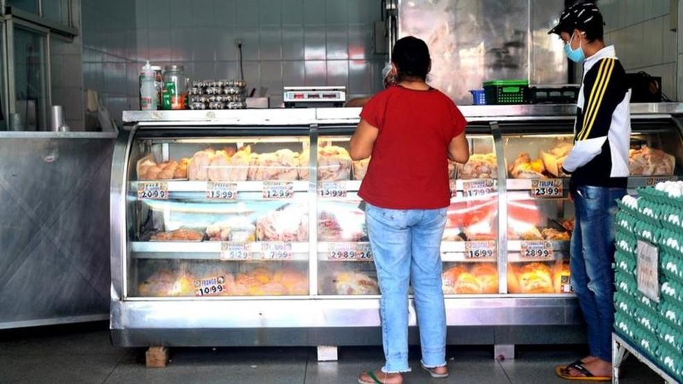 Depois de quatro tentativas, Lindinalva encontrou um local que tinha carcaças e pele de frango para vender — Foto: FELIX LIMA/ BBC NEWS BRASIL