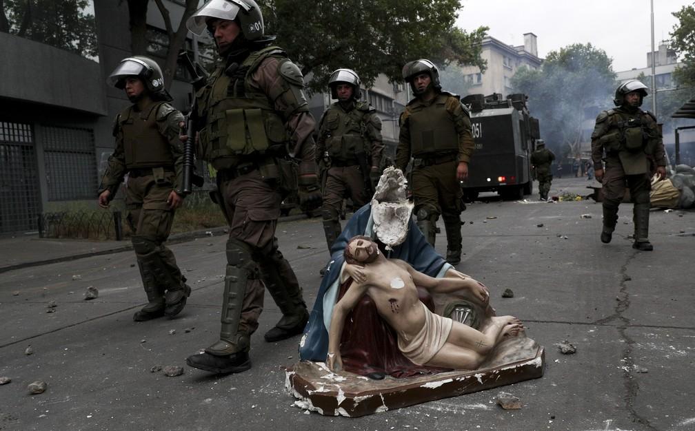 Imagem em igreja destruída durante protestos em Santiago, no Chile, permanece nas ruas enquanto policiais passam ao lado nesta sexta-feira (8) — Foto: Esteban Felix/AP Photo