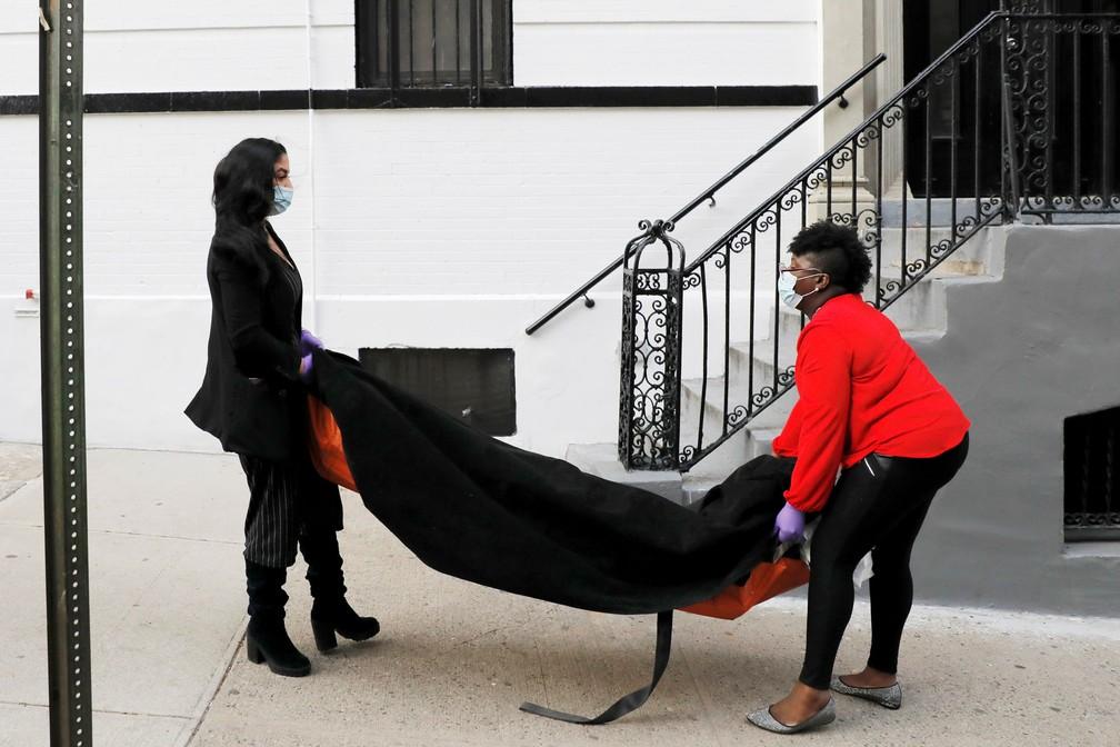 A gerente Alisha Narvaez, de 36 anos, e a diretora funerária Nicole Warring, de 33, carregam uma pessoa falecida para o porão de uma casa funerária no Harlem, em Nova York, onde os corpos são armazenados e preparados para os serviços funerários durante o surto de Covid-19, em 2 de abril — Foto:  Andrew Kelly/Reuters