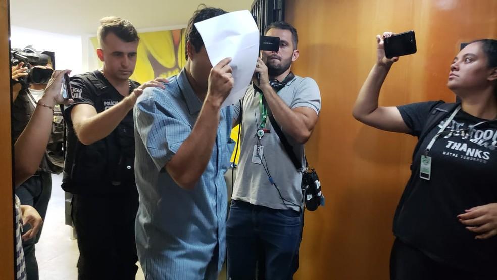 Preso deixa o Dema escondendo o rosto com papel — Foto: Carlos Amaral/G1