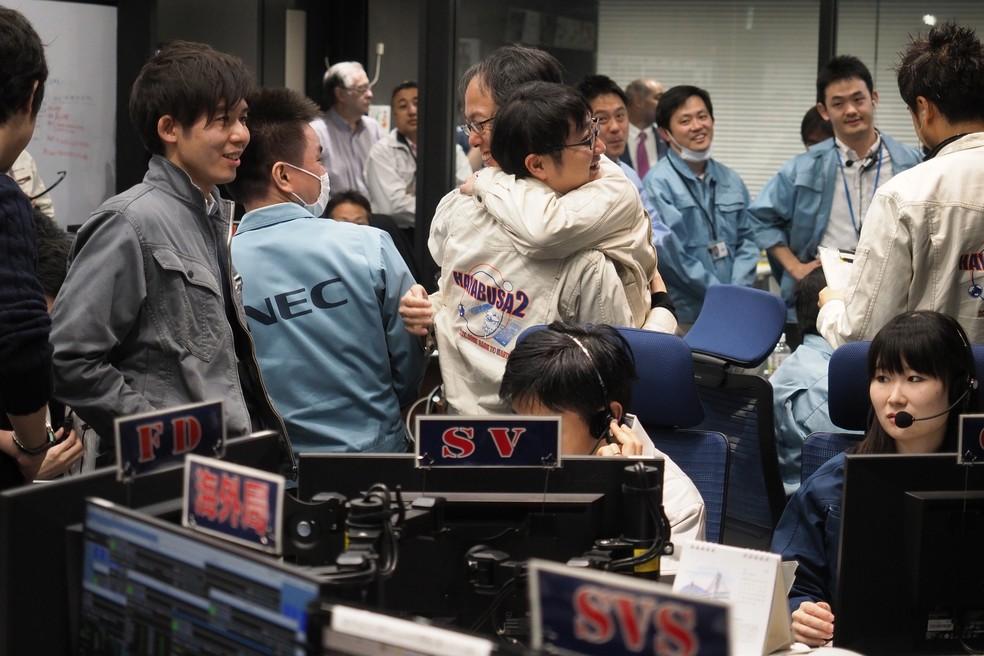 Engenheiro da Hayabusa2, Yuichi Tsuda (centro, à direita), comemora missão. — Foto: AFP / Isas-Jaxa