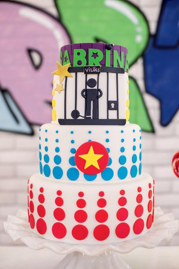 O bolo – No centro da mesa, o doce decorativo mostra no topo que o trabalho de uma super-heroína não termina até que o vilão esteja preso. (Foto: Thais Galardi/GNT)
