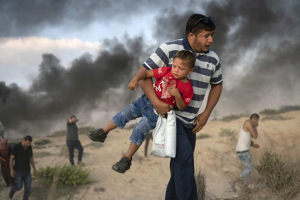 -  Manifestante palestino carrega um menino enquanto corre de uma bomba de gás lacrimogêneo. O artefato foi disparado por soldados israelenses durante p