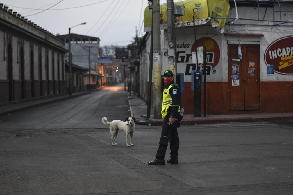 2 de abril - Policial usa máscara em uma rua vazia durante toque de recolher parcial, em Amatitlán, Guatemala — Foto: Johan Ordonez/AFP