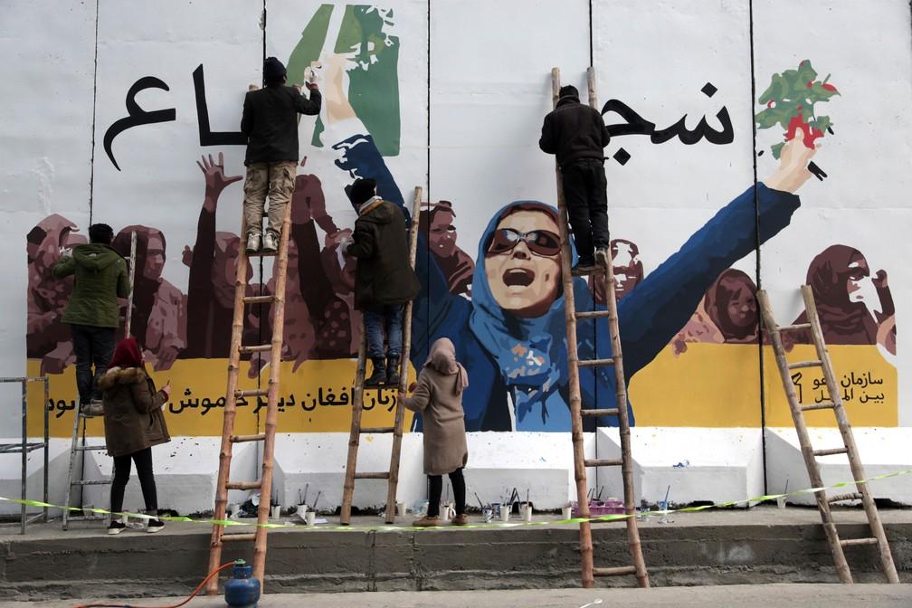 Artistas afegãos fazem grafite em muro do Ministério das Mulheres, em Cabul, nesta sexta-feira (8), Dia Internacional da Mulher — Foto:  Rahmat Gul/AP