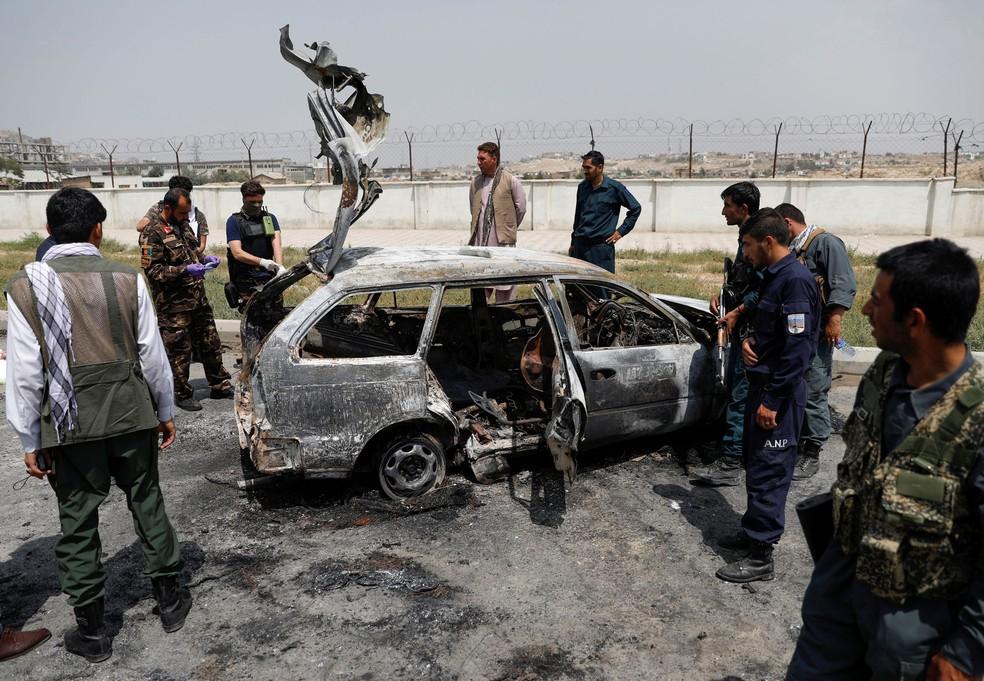 Autoridades afegãs inspecionam um veículo do qual os insurgentes dispararam foguetes, em Cabul, no Afeganistão, nesta terça-feira (18)   — Foto: Mohammad Ismail/ Reuters