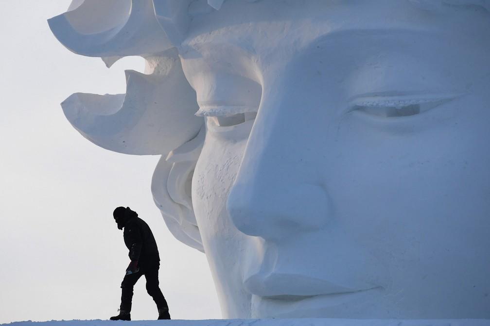 5 de janeiro - Um trabalhador passa por uma escultura de neve antes da abertura do festival anual 'Harbin Ice and Snow Sculpture, em Harbin, na província de Heilongjiang, no nordeste da China. O festival atrai milhares de visitantes anualmente (Foto: Greg Baker/AFP)