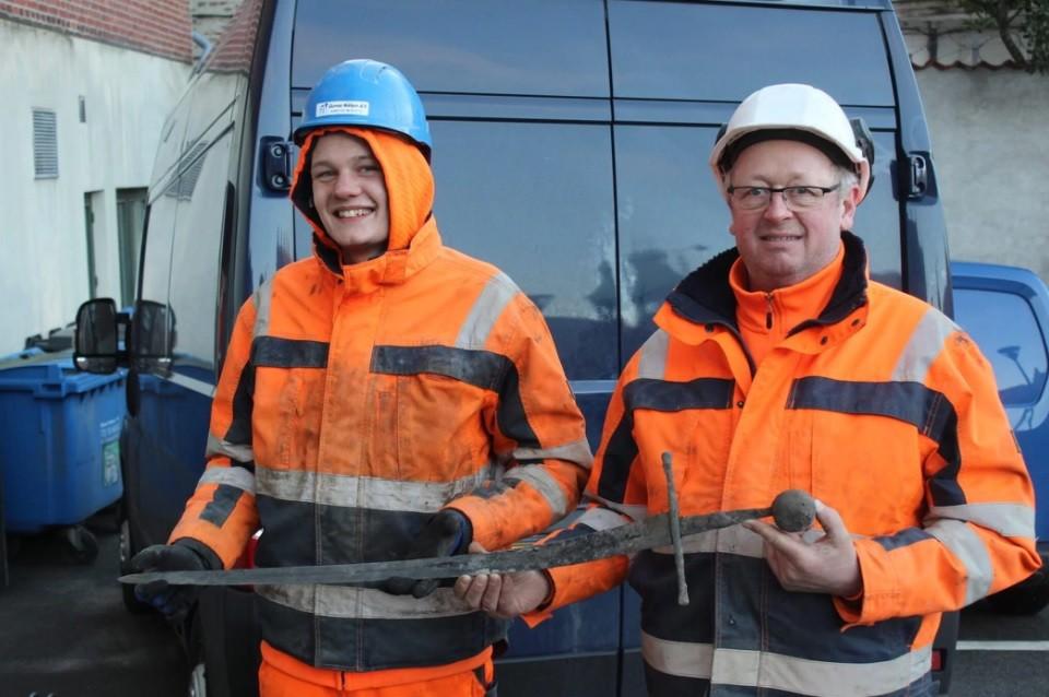 Os responsáveis pela descoberta exibem a espada encontrada (Foto: Divulgação/Nordjyllands Historiske Museum)