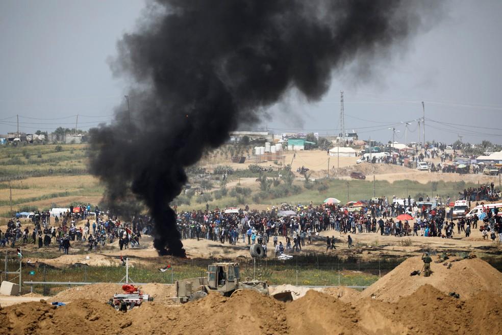 Soldados israelenses são vistos perto da fronteira entre Gaza e Israel nesta sexta-feira (6). Palestinos fazem protesto no local  (Foto: Amir Cohen/ Reuters)
