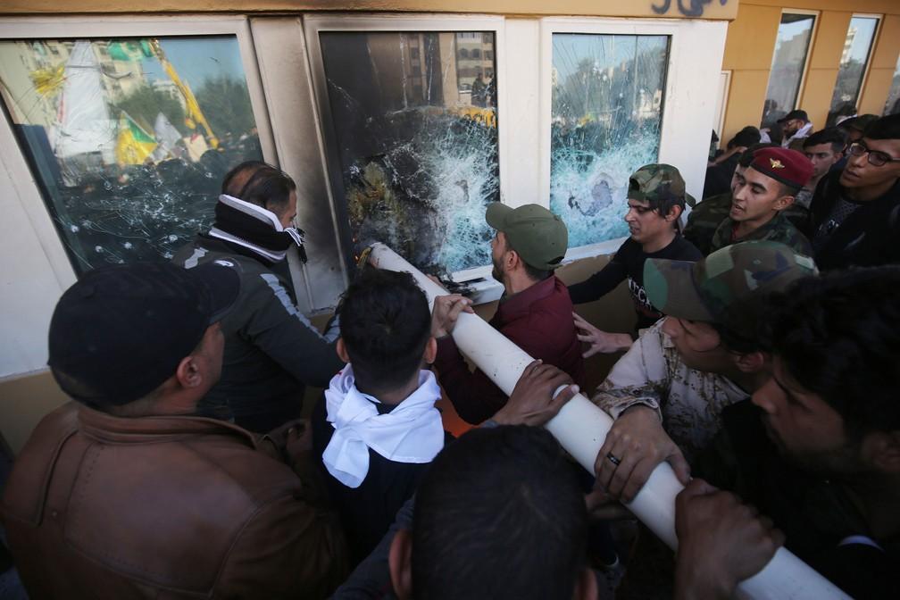Manifestantes iraquianos usam cano para quebrar janela da embaixada dos EUA, em Bagdá, nesta terça-feira (31)  — Foto: Ahmad Al-Rubaye / AFP