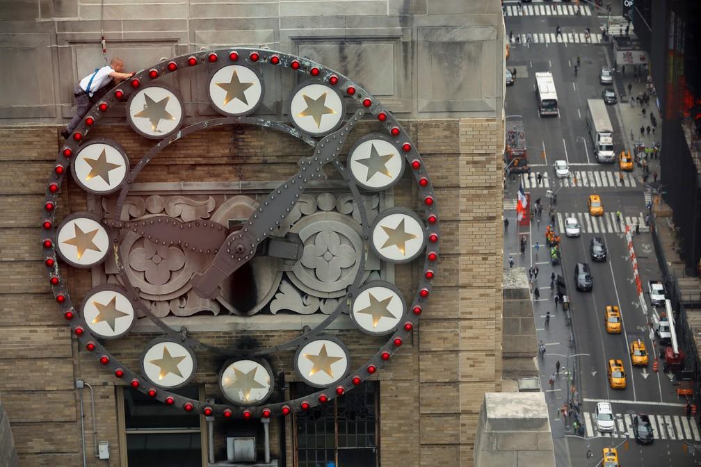 28 de maio - Um funcionário escala um relógio para trocar lâmpadas no prédio da Paramount na Times Square, em Nova York, nos EUA — Foto: Mike Segar/Reuters