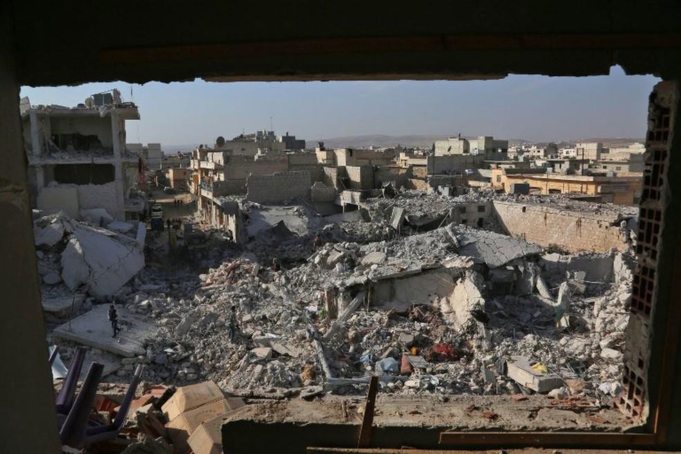 Sírios inspecionam nesta terça-feira (14) prédio destruído na cidade síria de Atareb, no oeste de Aleppo  (Foto: Zein Al Rifai / AFP )