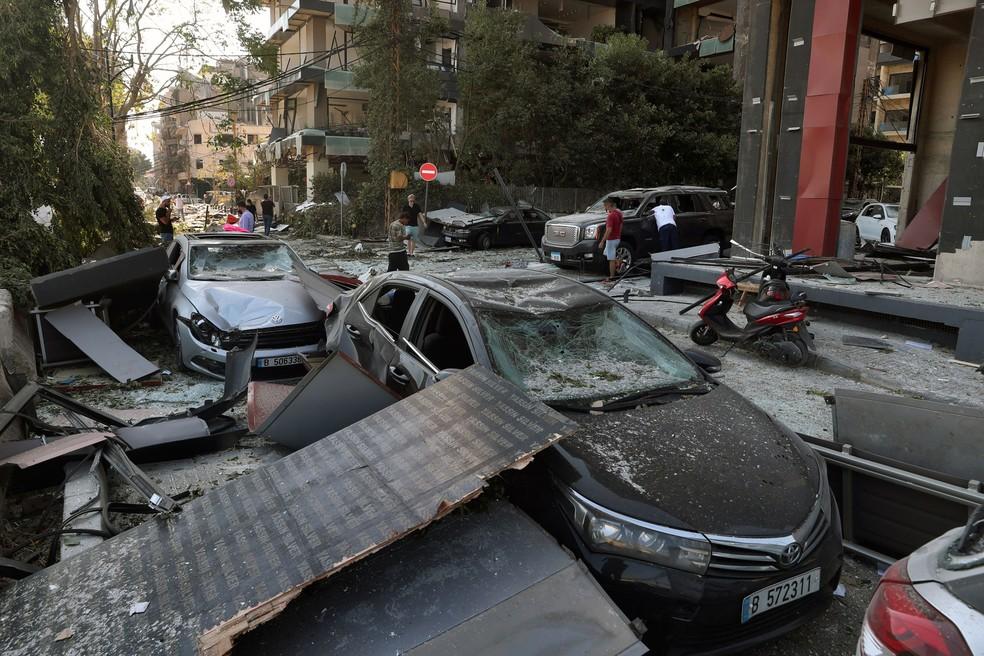 Pessoas olham quarta-feira (5) carros danificados após explosão, em Beirute, no Líbano  — Foto: Bilal Hussein/AP