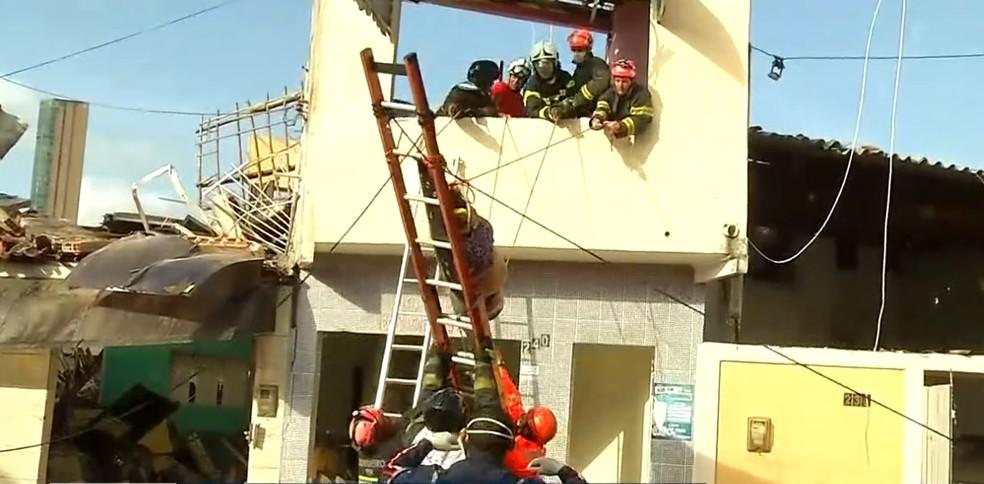 Vítima é tirada de primeiro andar após explosão atingir imóveis na Zona Leste de Natal.  — Foto: Reprodução/Inter TV Cabugi