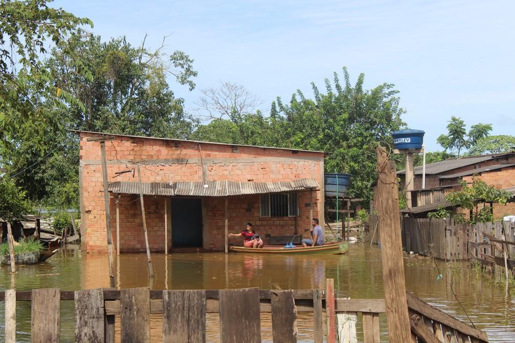 Família usa barco para navegar no quintal de casa — Foto: Cássia Firmino/G1