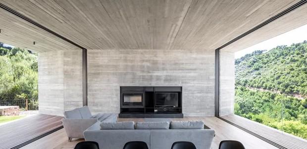 Na sala, a parede de concreto abriga a televisão e uma grande mesa de jantar completa o living. Destaque para os janelões de ambos os lados, que são responsáveis por esverdear a casa e completar a decoração minimalista (Foto: Nordest Arquitectura/ Reprodução)