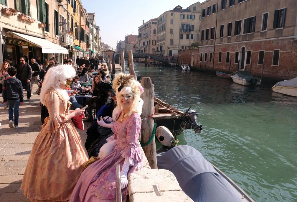 Mulheres mascaradas e com vestidos de época ao lado de canal em Veneza neste sábado — Foto: Manuel Silvestri/Reuters