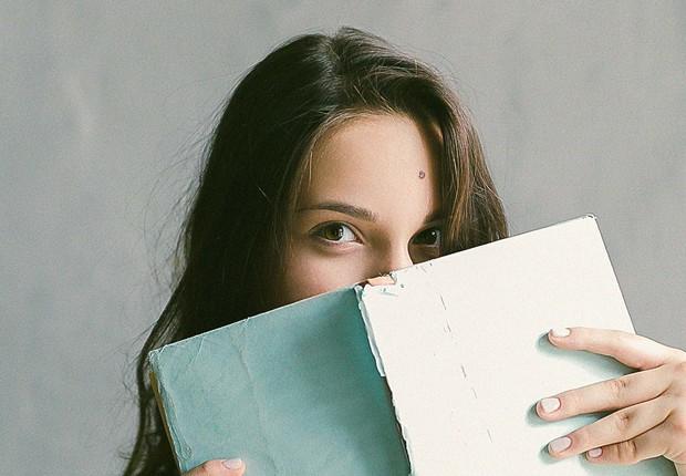 Mulher segurando livro em frente ao rosto (Foto: Daria Shevtsova/Pexels)