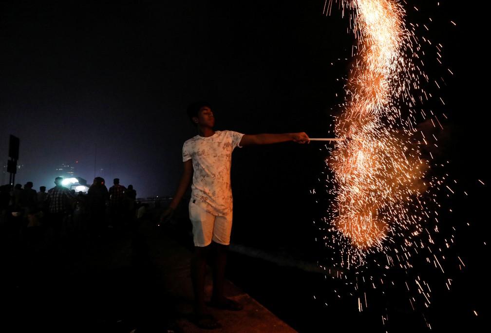Menino acende fogos em Colombo, no Sri Lanka, na quarta (1º). — Foto: Dinuka Liyanawatte/Reuters