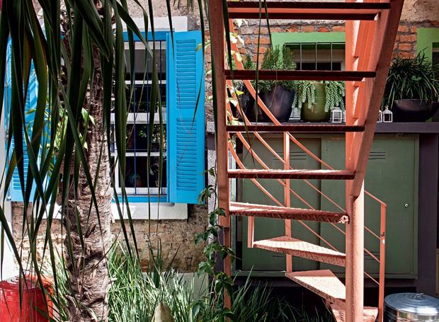 Embaixo da escada, bem na metade do terreno, palmeira traquicarpo com xanadus, moreias e aspargos-pluma. O pinguim de concreto é um xodó antigo dos donos. A janela do escritório ganhou demão de Curaçau Blue, da Suvinil (Foto: Gui Morelli/Editora Globo)