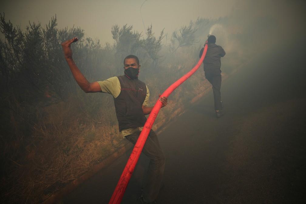 Voluntários lutam para conter incêndio fora de controle nesta segunda (19) nas encostas da Table Mountain, na Cidade do Cabo, na África do Sul — Foto: Mike Hutchings/Reuters