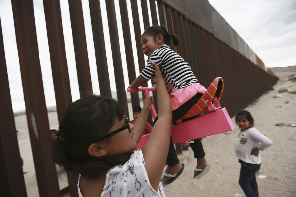Criança brinca na gangorra do lado mexicano da fronteira, em Ciudad Juárez, na terça-feira (30). — Foto: Christian Chavez/AP