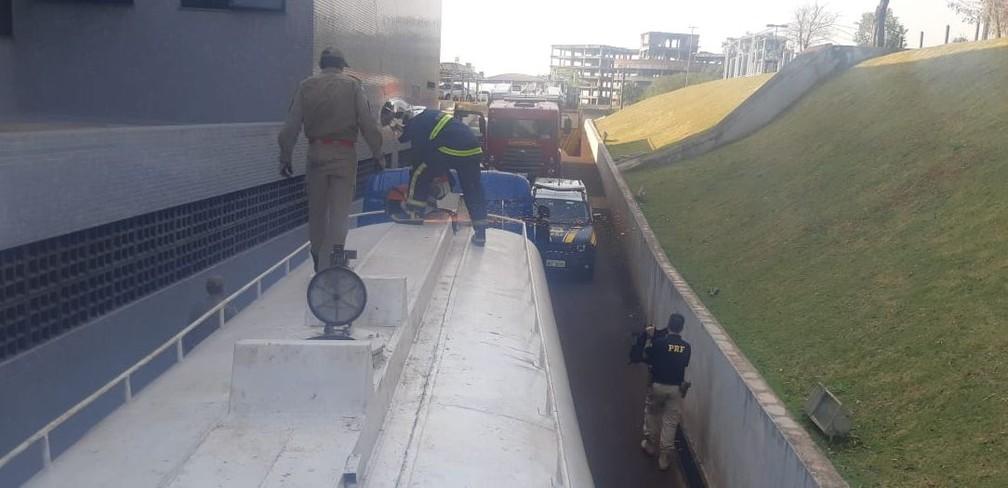 Policiais rodoviários e funcionários de concessionária precisaram usar ferramentas desencarceradoras para abrir o tanque do caminhão onde estavam 4,6 toneladas de maconha, na BR-277 — Foto: Divulgação/PRF