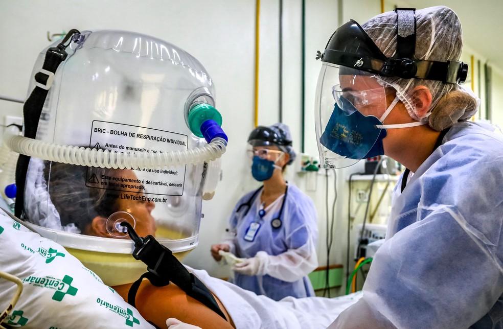 Profissionais de saúde com máscaras do tipo PFF2 cuidam de paciente internada com Covid-19 em UTI de São Leopoldo (RS), no dia 16 de abril. — Foto: Silvio Avila/AFP