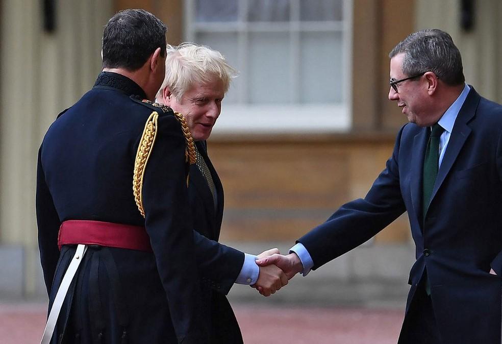 Após vitória em eleições gerais, premiê Boris Johnson é recebido pelo secretário particular da rainha Elizabeth II, Edward Young, ao chegar ao Palácio de Buckingham — Foto: Victoria Jones / AFP
