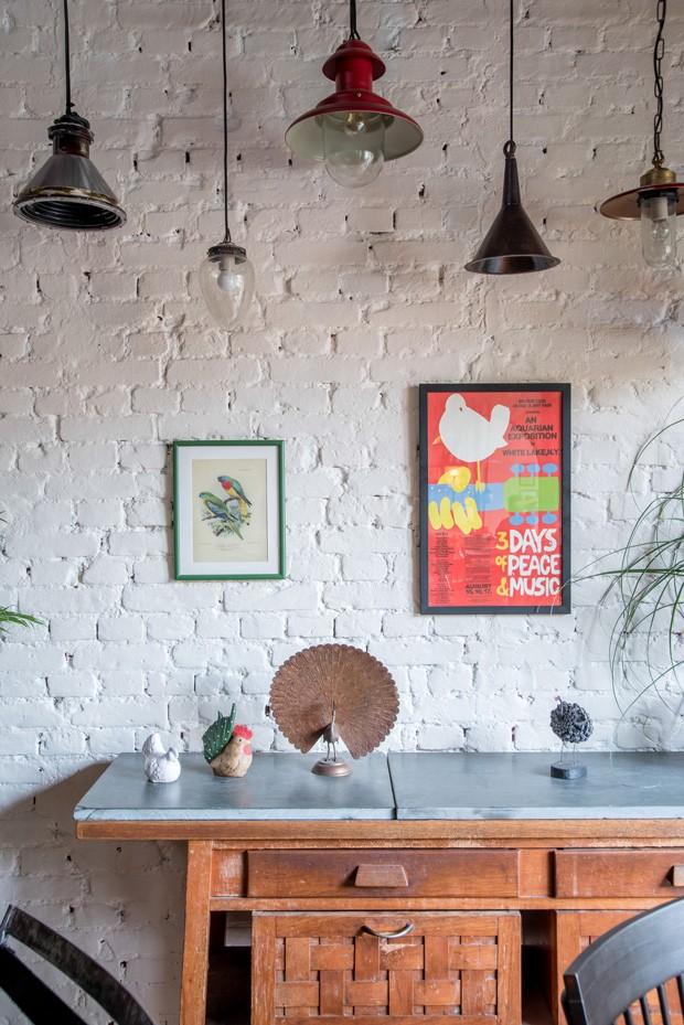 SALÃO | A mesa de madeira é de acervo pessoal: pertencia à mãe de um dos proprietários. Luminárias da Forja Recicla Design. (Foto: Julia Herman / Divulgação)